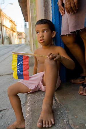 Justin Riley > A young Cuban plays with a Venezuelan flag on the streets of